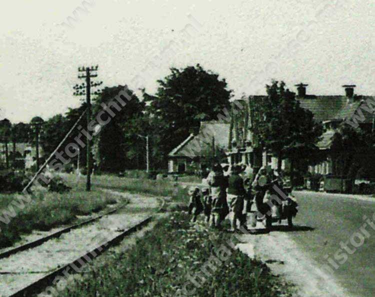 Precies midden op de foto, links van het groepje mensen is het oude boerderijtje zichtbaar.